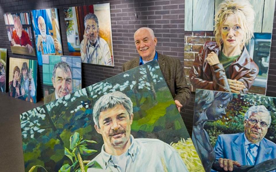 Joep Gierveld met enkele van de portretten die hij maakte van bekende Almeloërs. Foto Wouter Borre